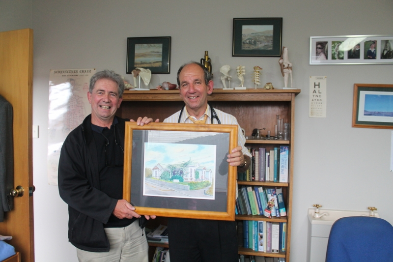 Dr Peter Borrie accepts the watercolour painting on behalf of Roslyn Medical Centre from artist Ron Esplin.